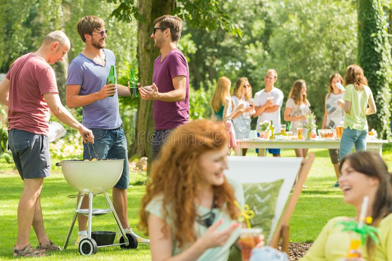 Friends grill and laugh in park royalty free stock photo
