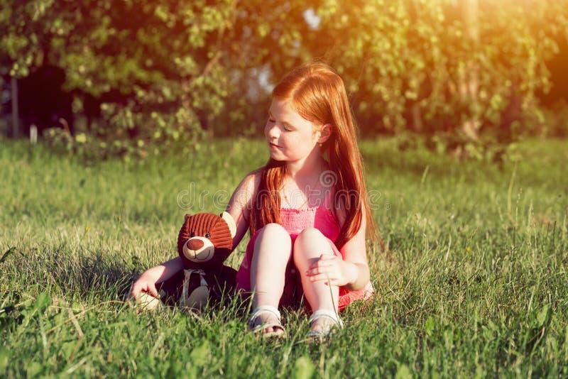 Redhead girl with teddy bear stock image