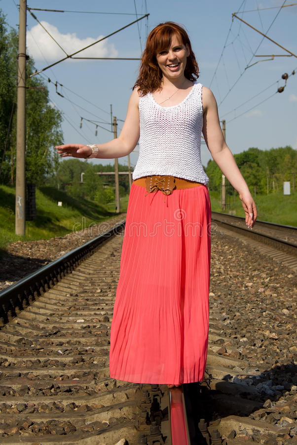 Redhead Girl Walks On The Rails Royalty Free Stock Photography