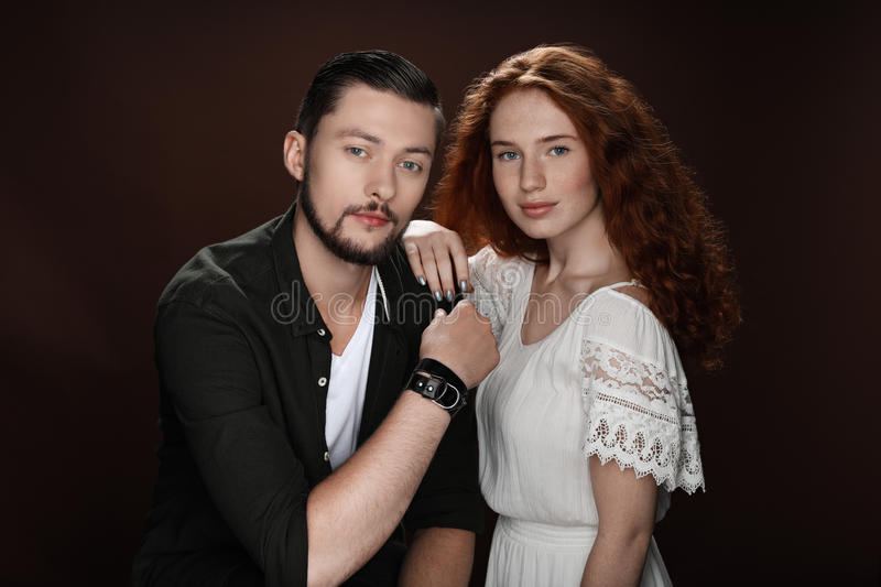 Redhead girlfriend and bearded boyfriend posing for studio shot. Isolated on brown stock photo