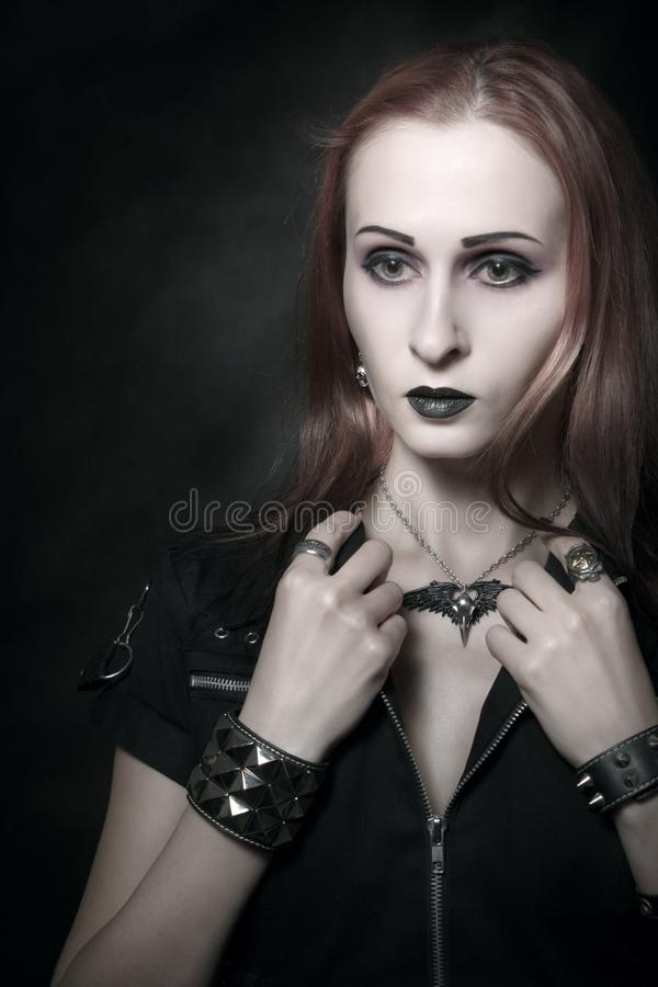 Redhead gothic girl. Gothic girl in dark clothes posing over dark background royalty free stock photo