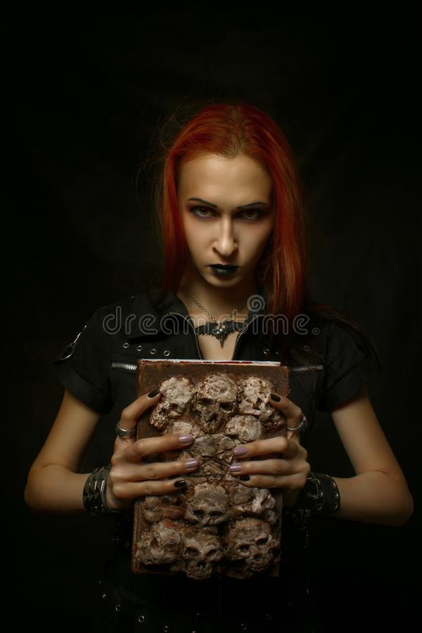 Possessed by demons. Redhead gothic girl with old grunge horrible book posing over dark background royalty free stock image