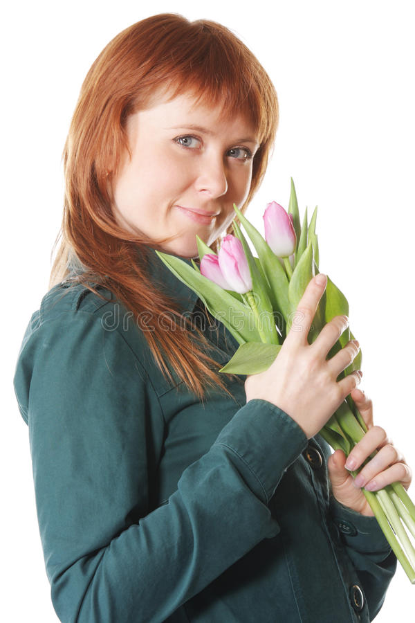 Redhead in green with pink tulips royalty free stock image