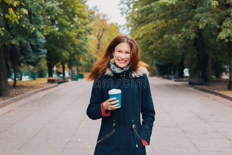 Redhead happy woman walking through the park alley, holding a blue paper cup of coffee or tea royalty free stock image