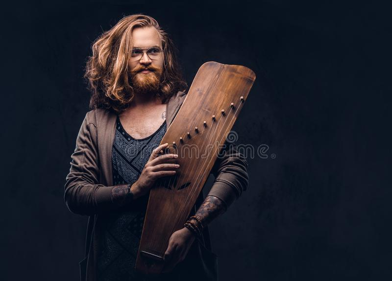 Redhead hipster male with long luxuriant hair and full beard dressed in casual clothes holds a Russian traditional. Musical instrument - gusli. Isolated on a stock photo