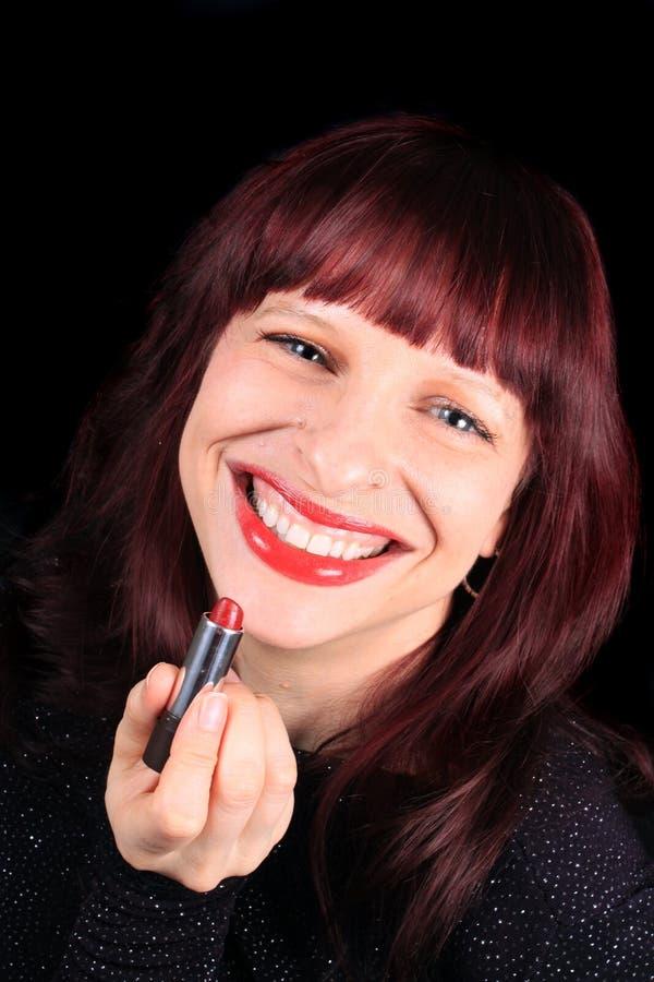 Redhead holding lipstick tube stock image