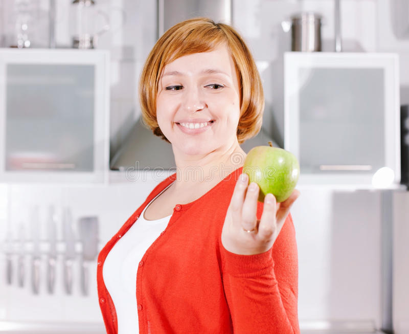 Download Redhead Housewife With Apple In Kitchen Stock Image - Image of looking, fruit: 39509133