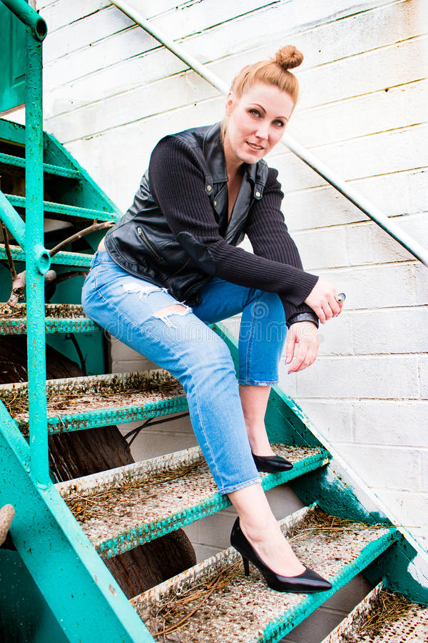 Redhead James Dean Woman. Fashionable redhead with a topknot hairstyle sitting on a metal teal staircase royalty free stock photography