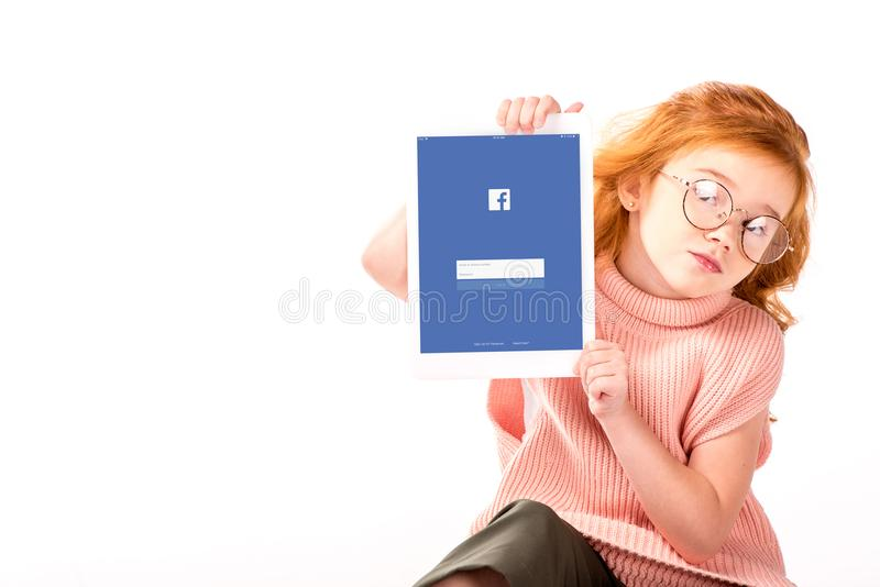 Redhead kid sitting and showing loaded facebook page on tablet. Isolated on white royalty free stock photo