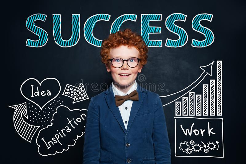 Redhead little boy in glasses and suit against hand drawing sketch and success text. Business idea and success concept royalty free stock photography