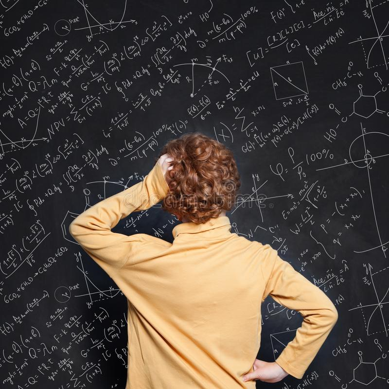 Redhead little boy thinking and looking at blackboard background with science formulas royalty free stock photo