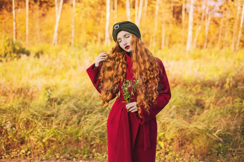 Redhead model in autumn clothes. Fabulous redhead woman with long curly hair in red coat on autumn background. Girl on fabulous background of deciduous forest stock photo