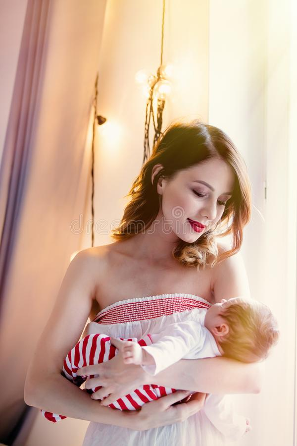 Redhead mother with new born child. stock image