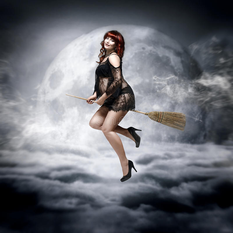 Redhead pregnant woman flying on a broom royalty free stock photography