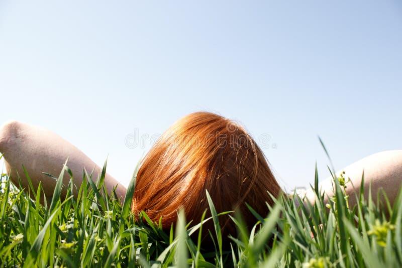 Redhead que pone en la hierba que mira para arriba imagen de archivo