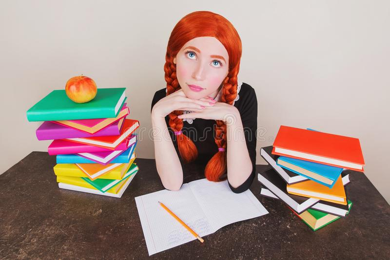Redhead schoolgirl in school uniform sits at desk on gray background. Colored text books on table. The apple lies on book. Back to school. Notebook and pencil stock photo