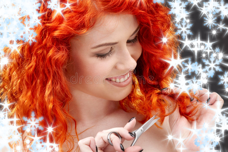 Redhead with scissors. Picture of lovely redhead with scissors and snowflakes royalty free stock photography