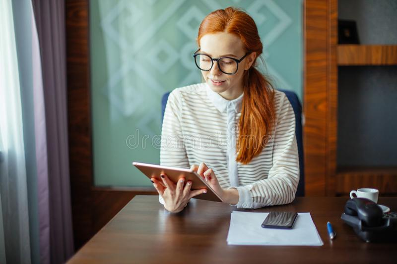 Redhead smiling young female manager using modern digital tablet at office stock images