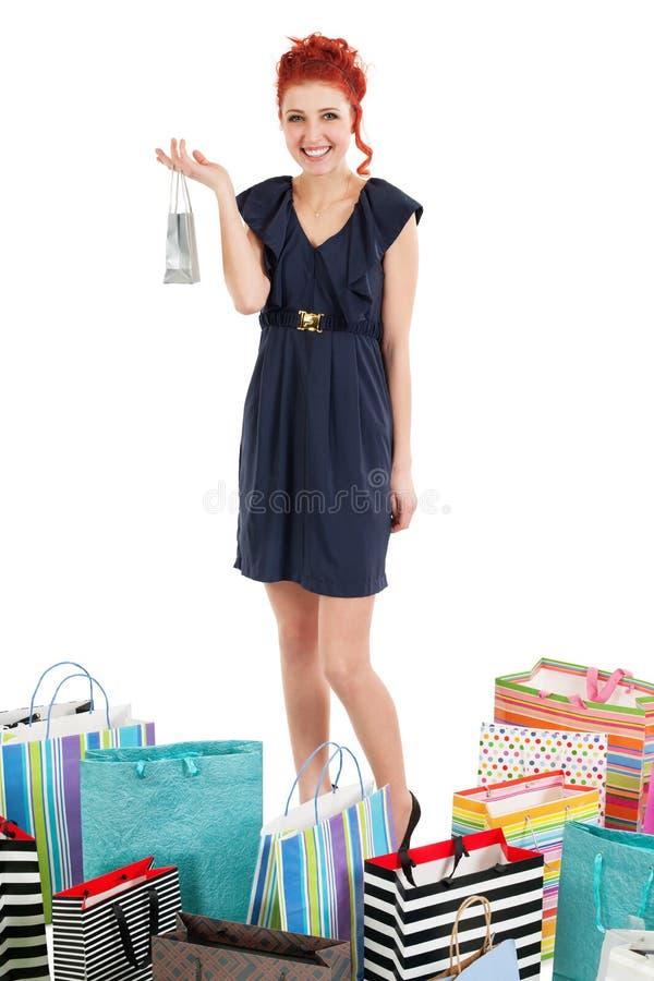 Redhead som plattforer med shoppingpåsar arkivbild
