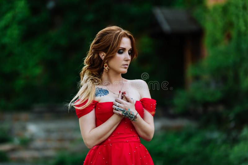Redhead woman in red dress near the castle stock photography