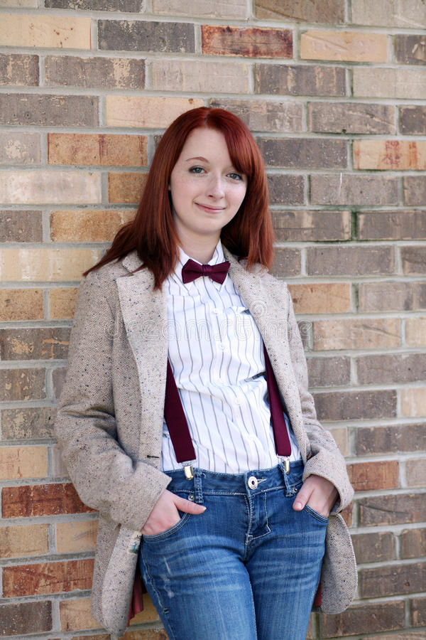 Redhead teen girl against brick wall royalty free stock photography