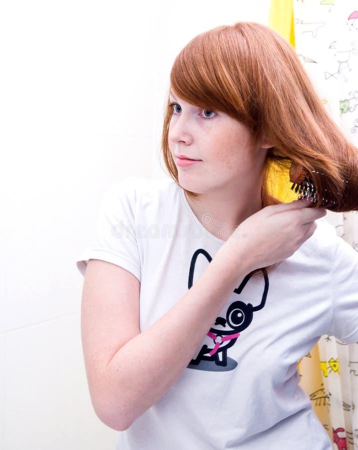 Redhead teen girl doing her hair stock photography