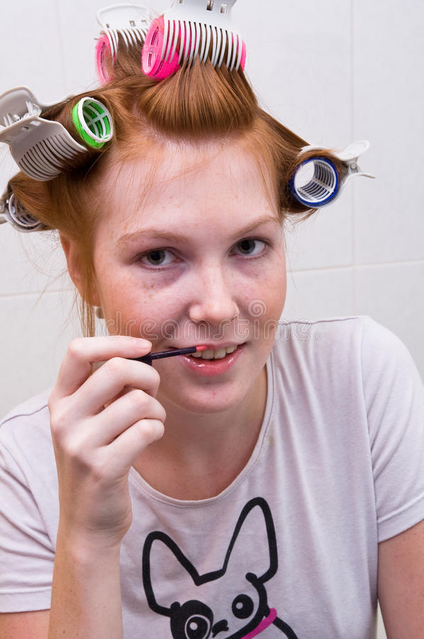 Redhead teen girl doing makeup royalty free stock images