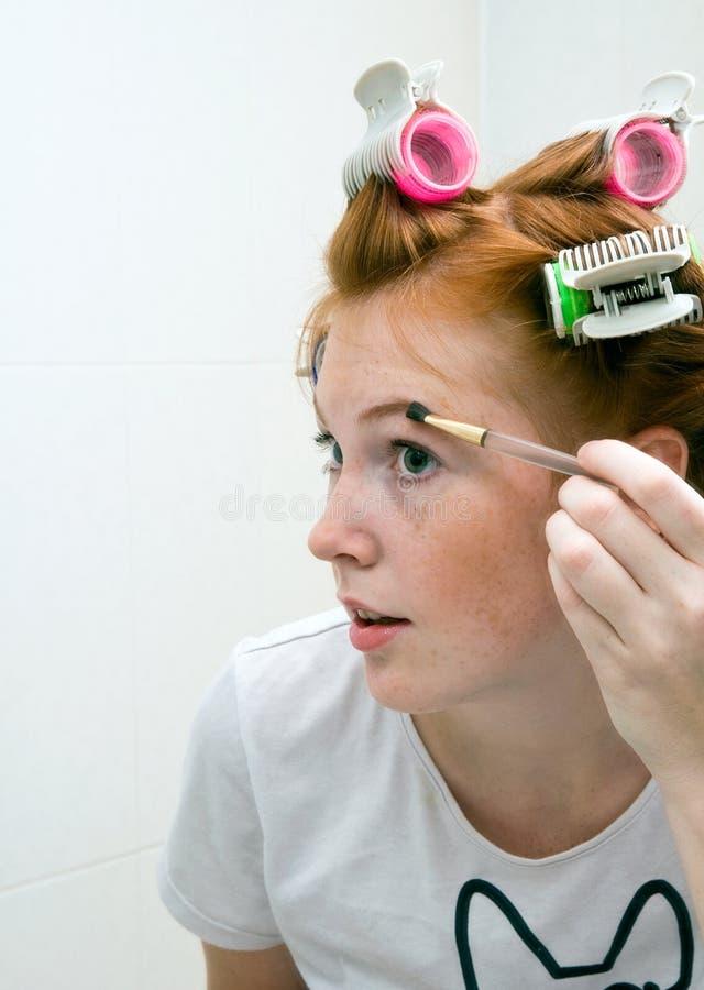 Redhead teen girl doing makeup stock photos