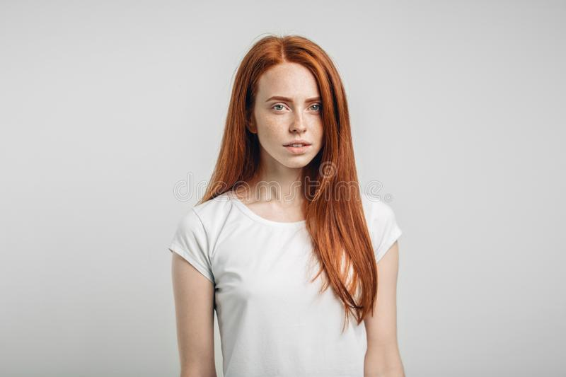 Redhead girl with healthy freckled skin looking at camera stock photo