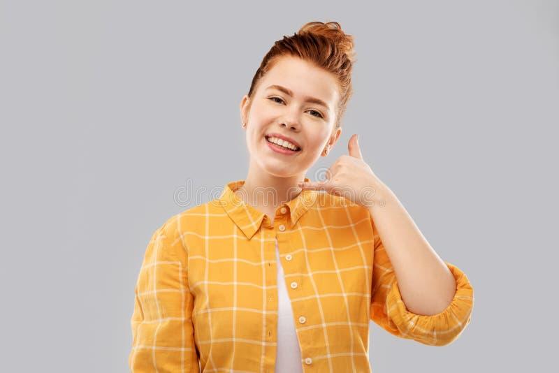 Redhead teenage girl making phone call gesture royalty free stock photos