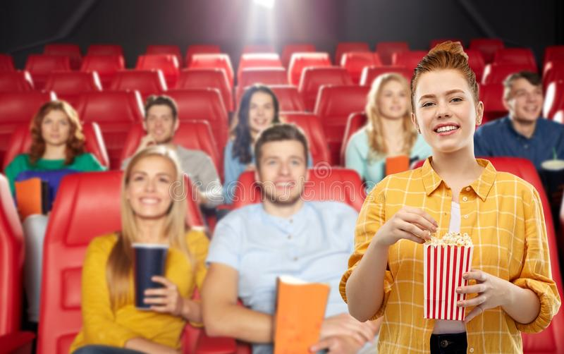 Redhead teenage girl with popcorn at movie theater stock images
