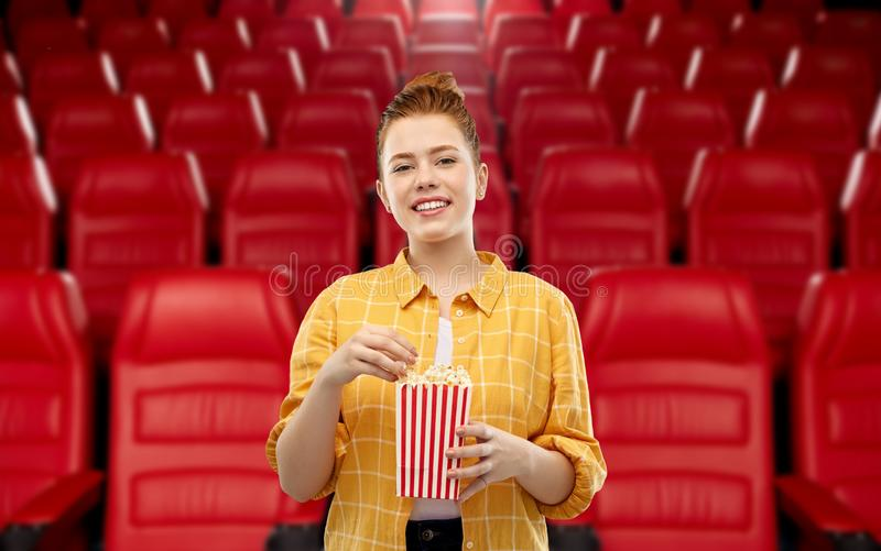 Redhead teenage girl with popcorn at movie theater stock image