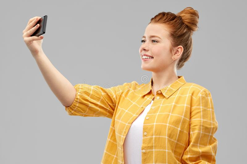 Redhead teenage girl taking selfie by smartphone. Technology and people concept - smiling red haired teenage girl in checkered shirt taking selfie by smartphone royalty free stock photography