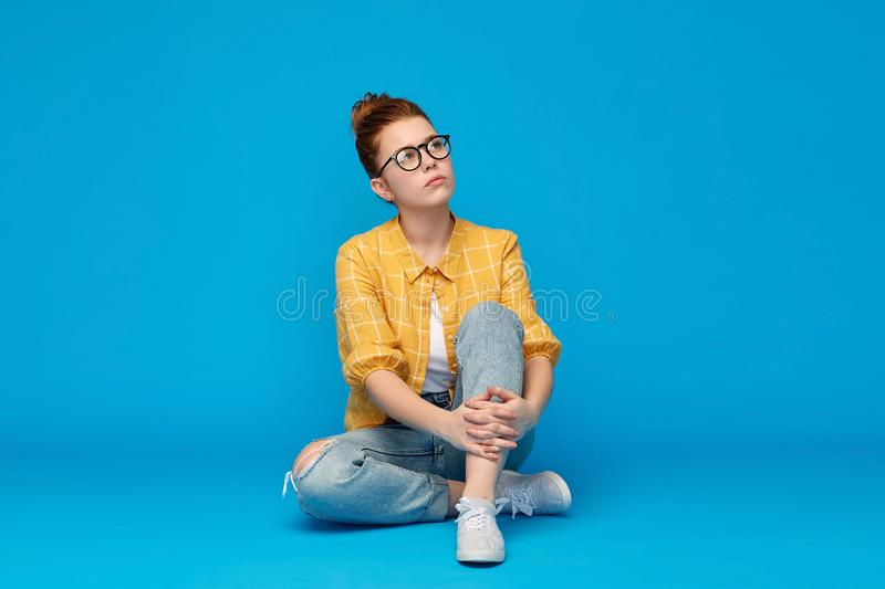 Redhead teenage student girl in glasses dreaming royalty free stock images