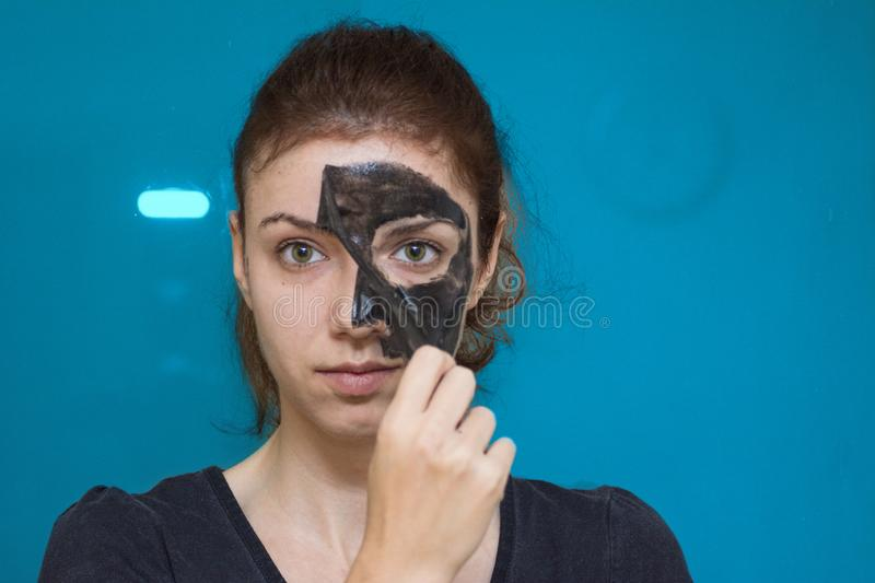 Charcoal peeling mask. Redhead using a black charcoal peeling mask for her face royalty free stock image