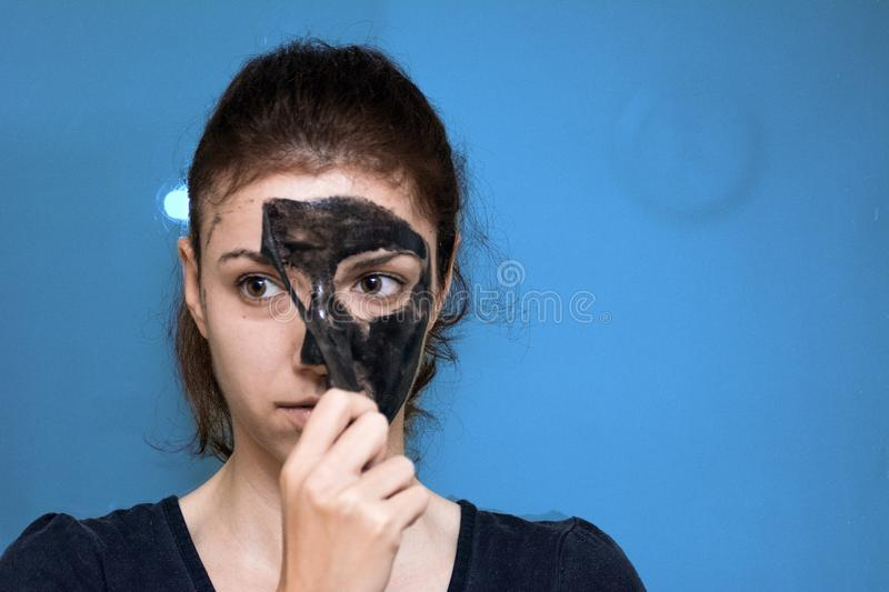 Charcoal peeling mask. Redhead using a black charcoal peeling mask for her face stock image