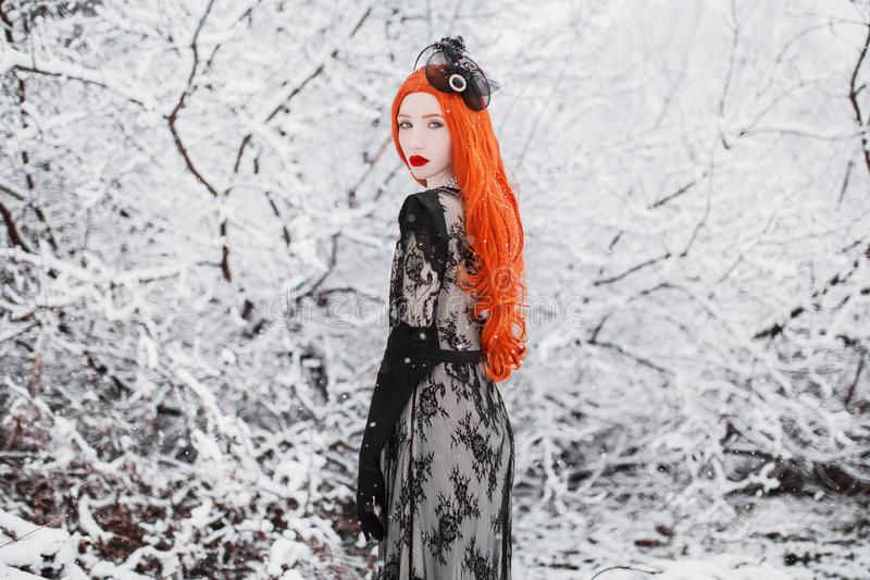 Redhead vintage girl with long red hair on winter background. Awesome winter snow fall. Redhead woman in black vintage dress and w. Ith long gloves on a stock photography