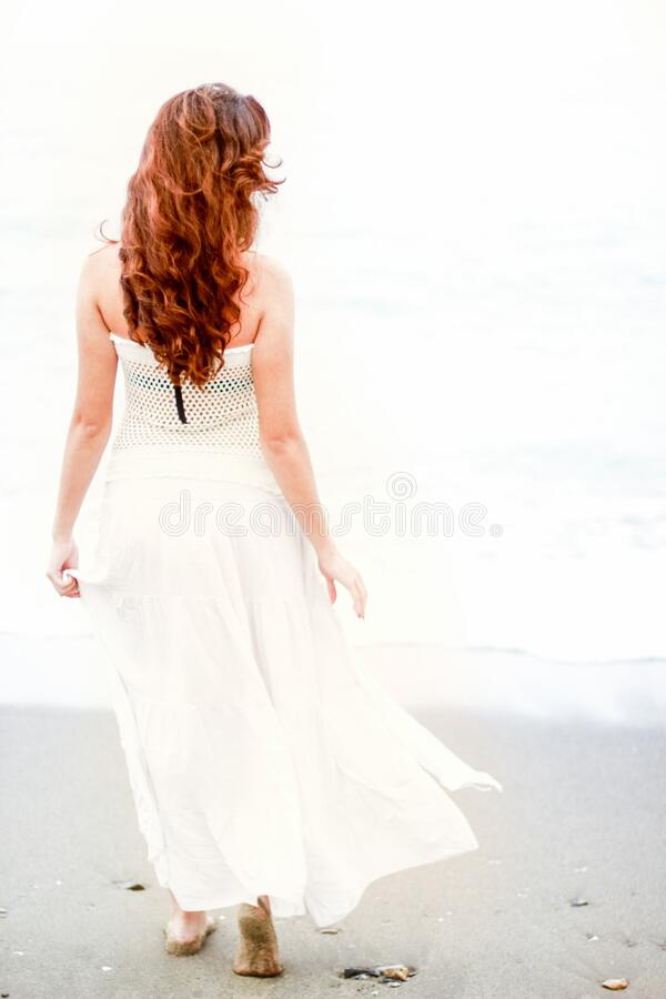 Redhead woman on beach stock photography