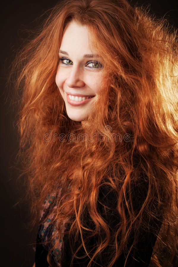 Redhead woman with beautiful long hair. Young woman with beautiful long fluffy hair royalty free stock photography