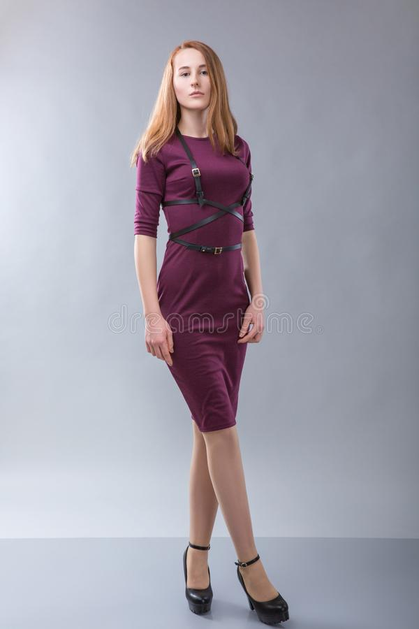 Redhead woman in burgundy dress with black belt standing in photostudio on gray background royalty free stock image