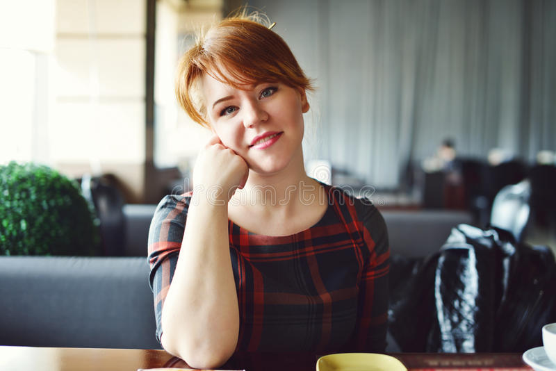 Redhead woman in cafe stock photo