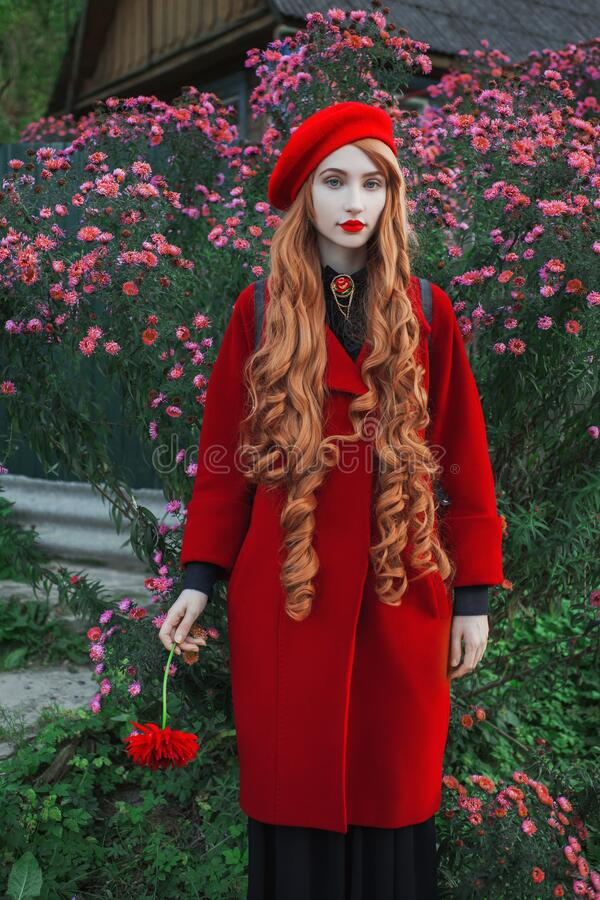 Redhead woman in coat on flower background. Fashion model with long red hair with red flower in hand. Turban and stylish coat. Red stock images
