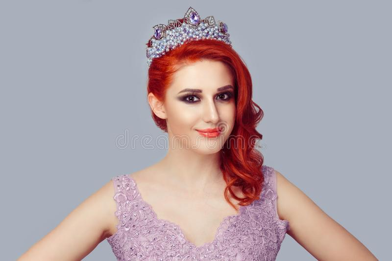 Redhead woman in crown with purple pearls and crystals in violet color lace dress stock image