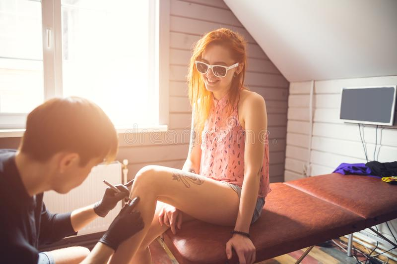 Redhead woman decided to get tattoo. Woman in sunglasses and red hair decided to get a tattoo. women sitting on the couch. men makes a sketch of the pattern on stock photography