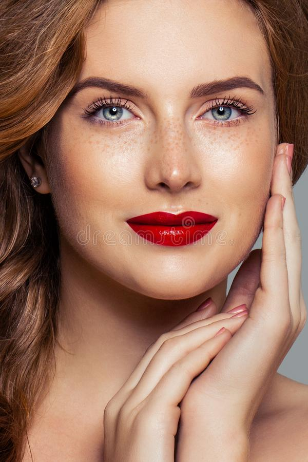 Redhead woman face closeup portrait. Ginger hair, freckles, red lips makeup and red nails royalty free stock photos