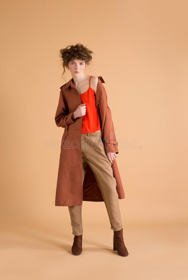 Redhead woman with freckles wearing beige pants, orange shirt and pants korichnivoe coat on a beige background. stock image