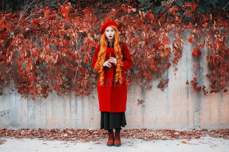 Redhead woman hol flower in red coat on autumn background. Girl on background wall with orange autumn leaves. Red turban and. Stylish coat. Fashion model with stock images