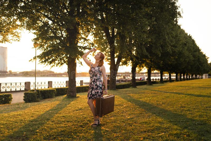 Redhead woman holding traveling suitcase in the sunset by the river in a new City - Traveler and explorer royalty free stock photos