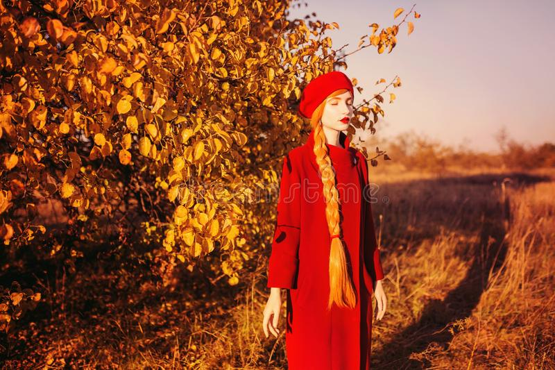 Redhead woman with long hair in red coat on autumn background. Girl with long braided plait on background of forest with orange. Autumn leaves. Leaves fall from stock photography