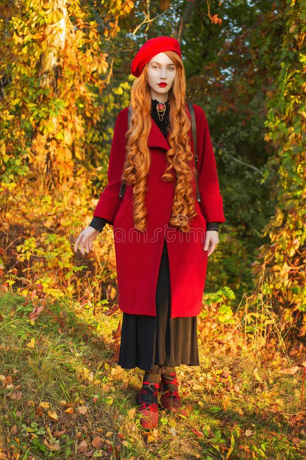 Redhead woman with long hair in red coat on autumn background. Girl with red hair on background of forest with orange autumn stock photo